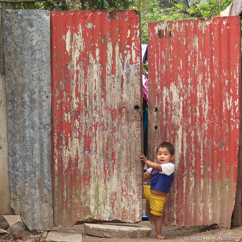 Rudy Giron: Antigua Guatemala &emdash; Boy opening a red lamina doorway around Antigua Guatemala
