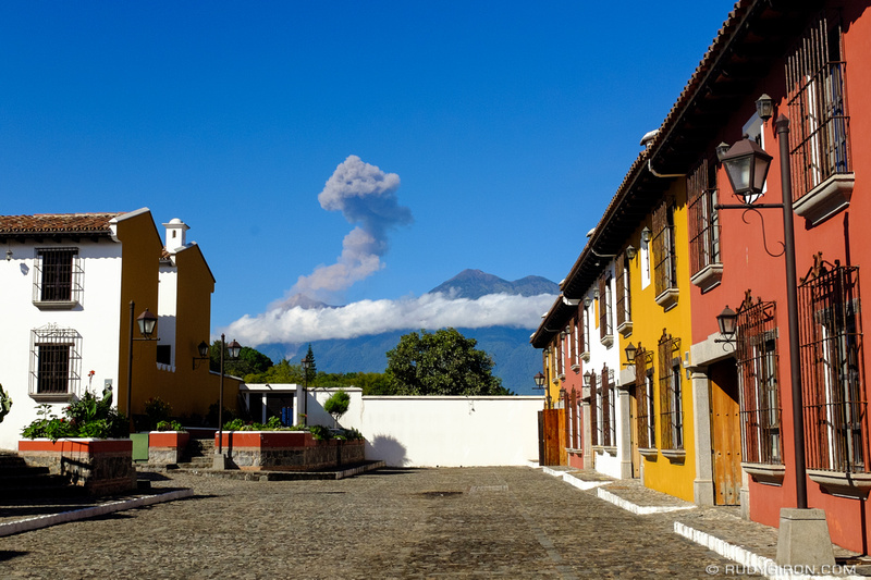 Rudy Giron: Antigua Guatemala &emdash; Fuego Volcano Erupting framed with colonial style houses