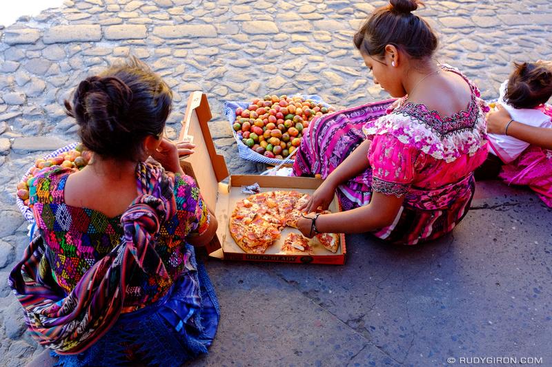 Rudy Giron: Antigua Guatemala &emdash; Maya women eating pizza on the streets